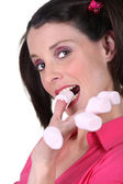 Woman eating marshmallows off her fingers — Stock Photo