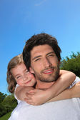 Dad giving his daughter a piggy back — Stock Photo
