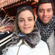 Couple on ski holiday stood by chalet - ストック写真