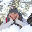 Stock Photo: Young woman playing with the snow in the park