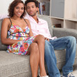 Couple sitting on sofa gray - Stock Photo