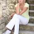 Blonde woman sitting on stairs — Stock Photo #9312340