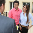 Estate-agent with young couple - Stock Photo
