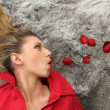 Laid woman blowing on rose petals — Stock Photo #9313601