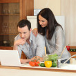 Couple looking at a laptop in their kitchen — Stock Photo