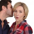 Man talking to woman's ear — Stock Photo