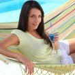 Woman with a cocktail in a hammock — Stock Photo