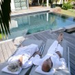 Stock Photo: Couple on loungers next to private pool