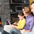 Family on a sofa in front of the fireplace — Stock Photo
