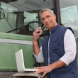 Farmer near a tractor with computer — Foto Stock