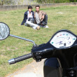 Foto Stock: Motorcycle parked on grass and couple