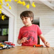 Stock Photo: Young boy playing with his toy cars