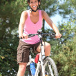 Woman cycling in the forest — Stock Photo
