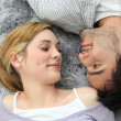 Couple lying on carpet — Stock Photo #9316812