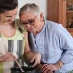 unga förbereder måltid till senior — Stockfoto