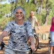 A 65 years old woman in first plan and three other doing bike in the forest - Stock Photo