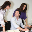Three colleagues gathered around desk — Stock Photo