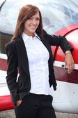 Proud woman in front of a plane — Stock Photo