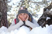 Young woman playing with the snow in the park — Stock Photo