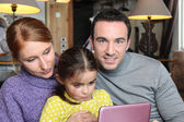 Family gathered on sofa with pink laptop — Stock Photo