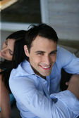 Young couple sat back to back on their porch — Stock Photo
