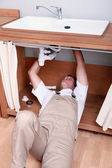Plumber fixing sink — Stock Photo