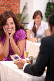 Man giving gift to woman in restaurant — Stock Photo