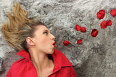 Laid woman blowing on rose petals — Stock Photo