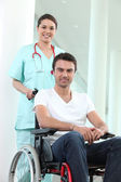 Nurse with disabled man in a wheelchair — Stock Photo