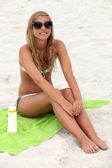 Girl sitting on the beach — Stock Photo