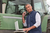 Farmer near a tractor with computer — Stock Photo