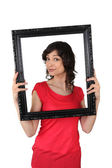 Brunette red tunic holding frame — Stock Photo