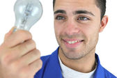 Young blue collar holding bulb — Stock Photo