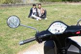Moto garée sur l'herbe et le couple — Photo
