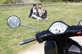 Motorcycle parked on the grass and couple — Stok fotoğraf
