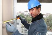 Manual worker measuring interior wall — Stock Photo