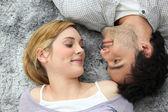 Couple lying on carpet — Stock Photo