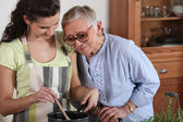 Young preparing meal to senior — Stock Photo