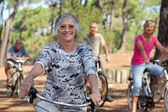 A 65 years old woman in first plan and three other doing bike in the forest — Stock Photo