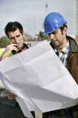 Foreman and colleague checking over plans — Stock Photo