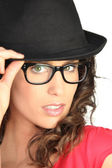Beautiful woman in a black hat and pair of thick rimmed glasses — Stock Photo