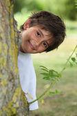 木の幹の後ろの男の子 — ストック写真