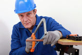 Artisan sawing copper pipe — Stock Photo