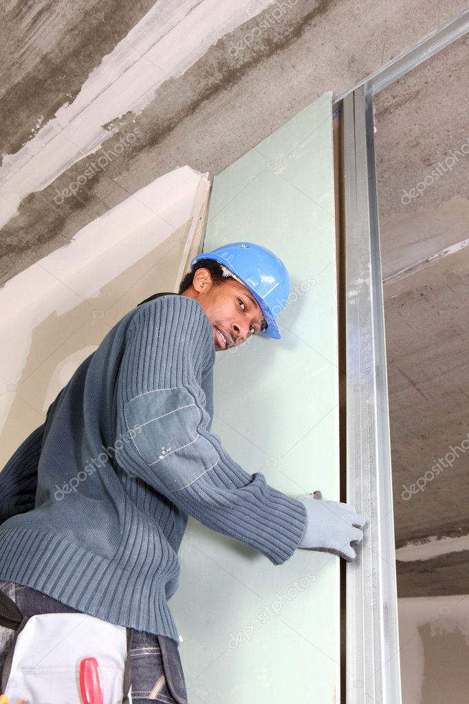 Young black carpenter at work fixing door indoors — Stock Photo #9310578