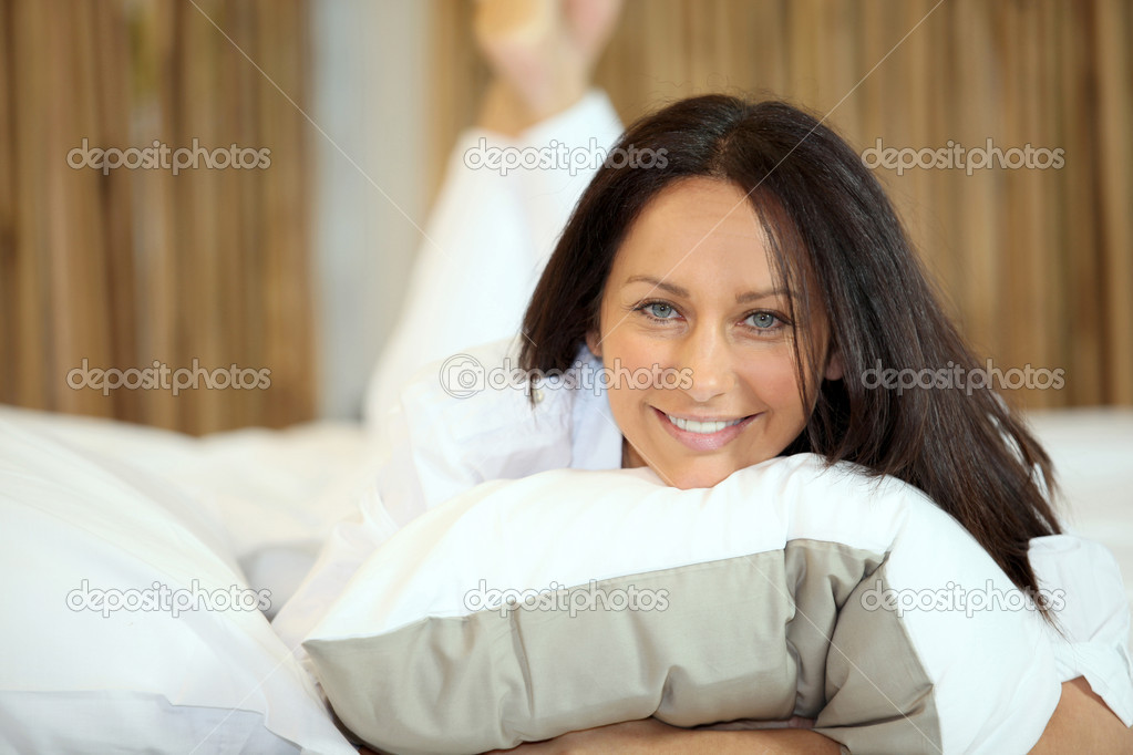 Attractive brunette layingon her bed — Stock Photo #9310675