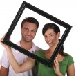 Silly couple with picture frame — Stock Photo #9320078
