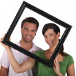 Silly couple with picture frame — Stock Photo
