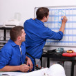 Manual workers writing on a calendar — Stock Photo #9320360