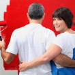 Stock Photo: Couple painting wall in red