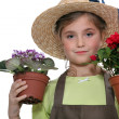 Little girl holding two plants in pots — Stock Photo
